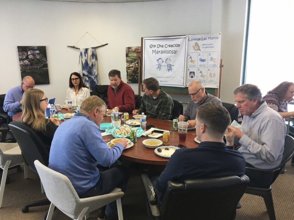The headquarters team eats around the table on Annual Mission Day