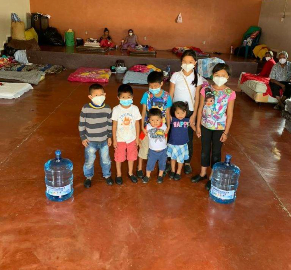 Children stand with bottles of safe water